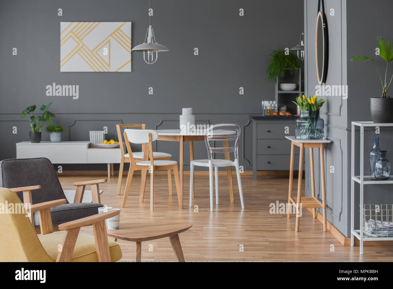 White chairs at dining table in grey apartment interior with yellow ...