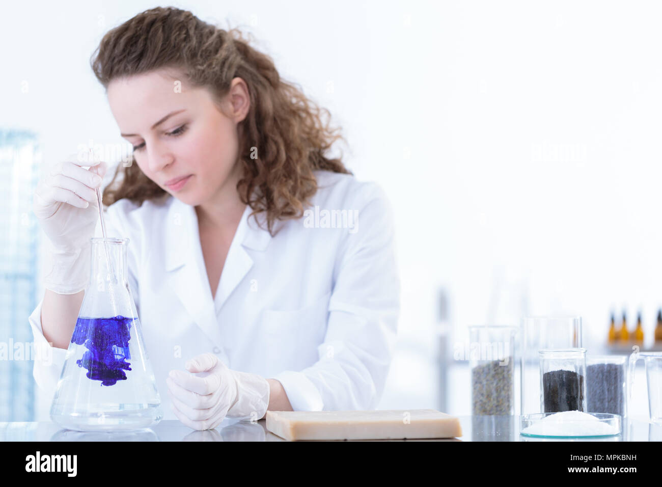 Chemist pouring substance into a flask with solution in the laboratory - Stock Image