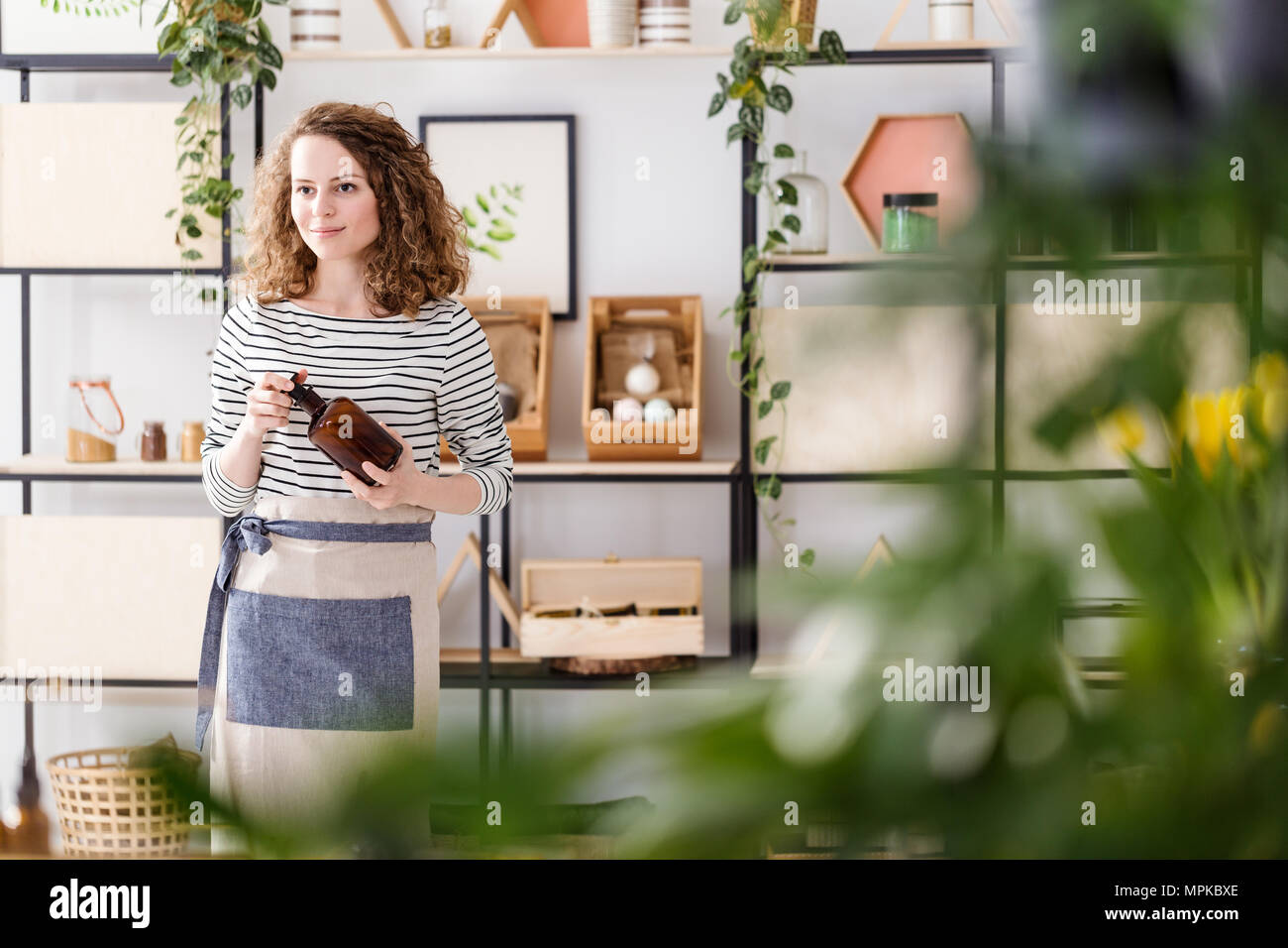Smiling woman with a brown bottle in a natural shop with organic products - Stock Image