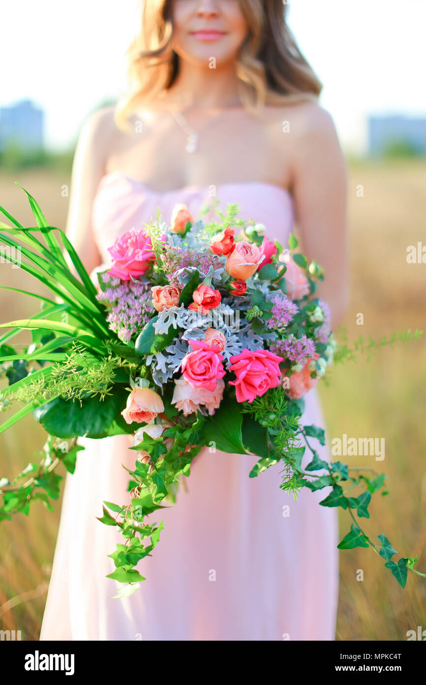 Pretty woman standing with bouquet of flowers wearing pink dress. Stock Photo