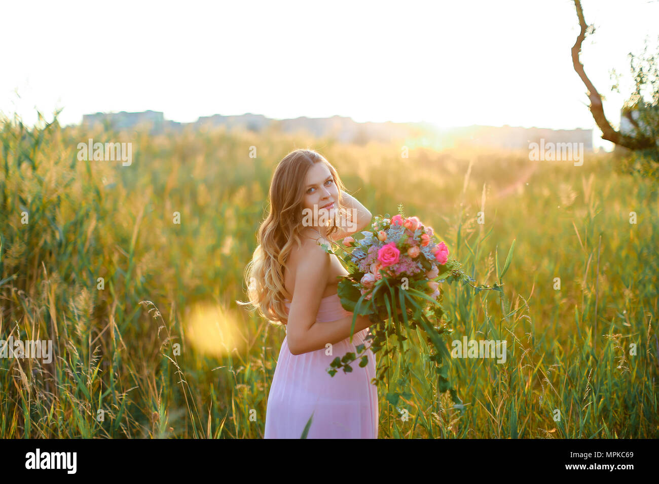 Pregnant young caucasian woman wearing pink dress with bouquet of flowers standing in steppe background. - Stock Image