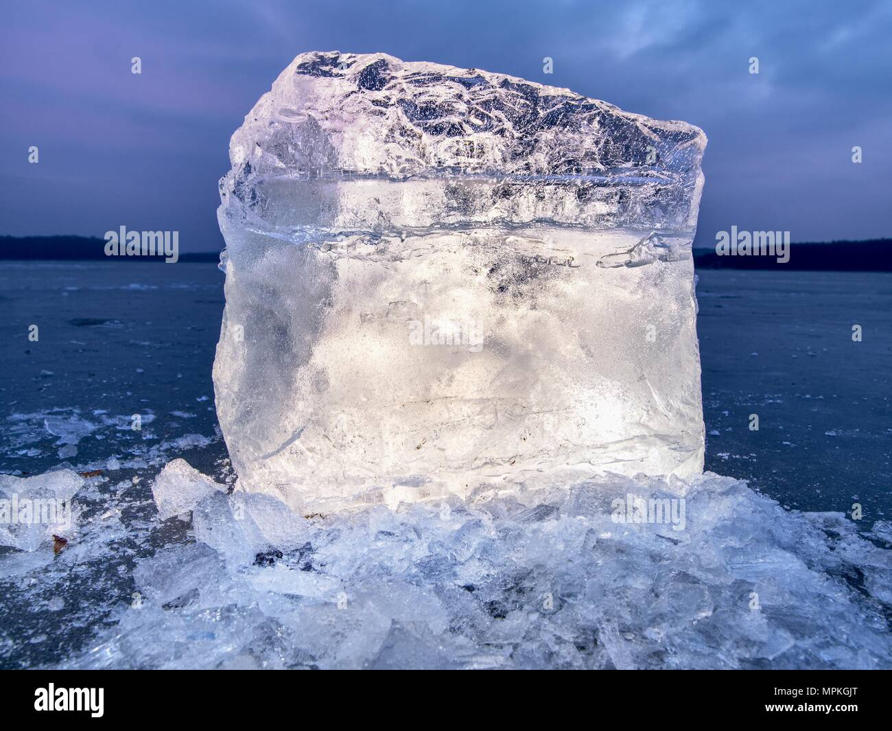 Arctic ice. A large piece of natural ice on a green blue flat ice of frozen lake, water bubbles texture. Shiny detail inside wonderful of transparent. - Stock Image