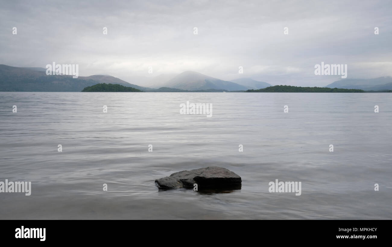 Moody loch lake atmospheric grey clouds dark water Lomond Scotland highlands landscape scene outdoors - Stock Image