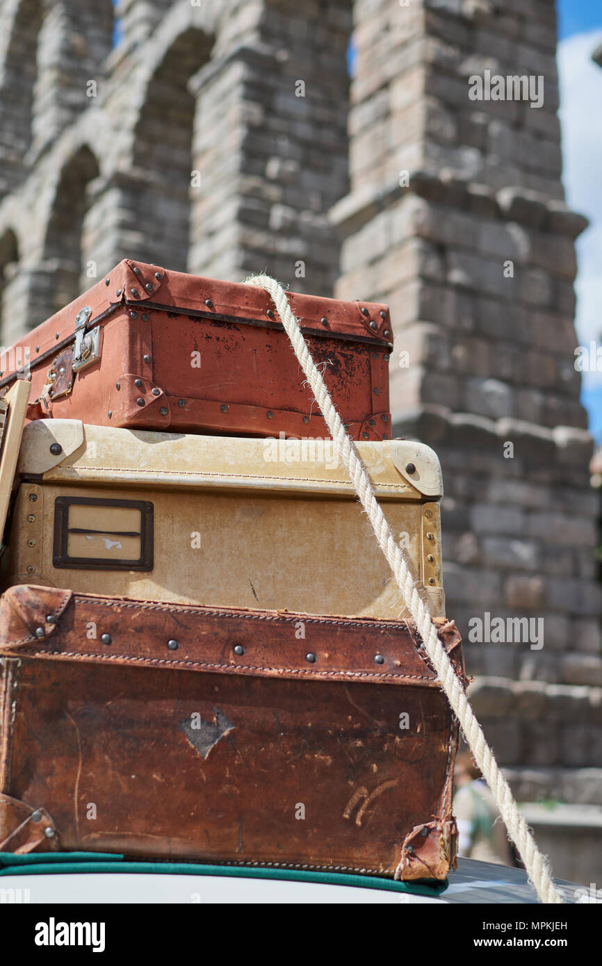 Close-up of old vintage travel suitcases fastened to the roof of a car with a rope and in the background the aqueduct of Segovia, Spain - Stock Image