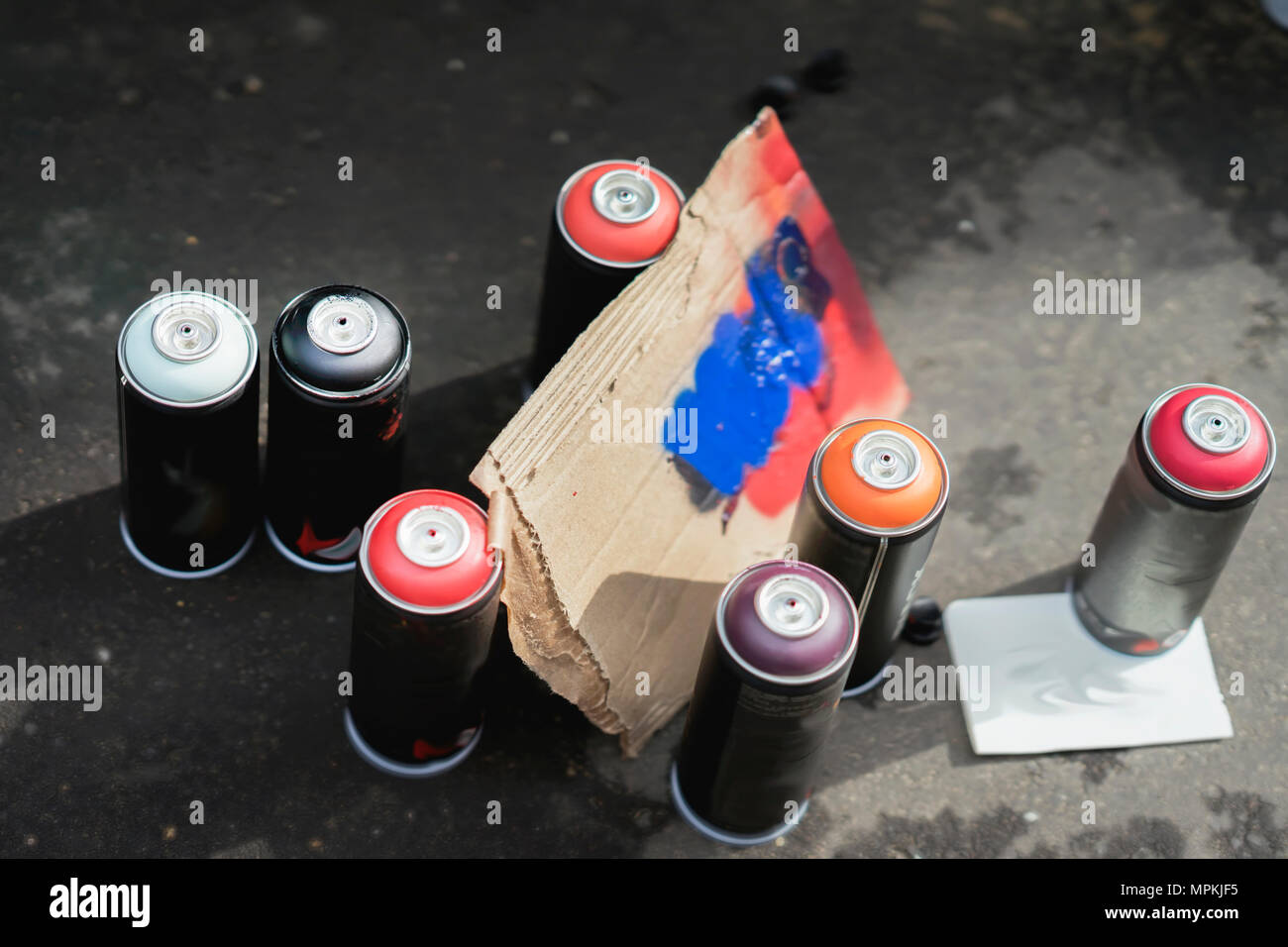 Aerosol metal cans of spray paint and cardboard palette for paint, graffiti on dark background of asphalt. Urban contemporary iconic culture of street youth Stock Photo