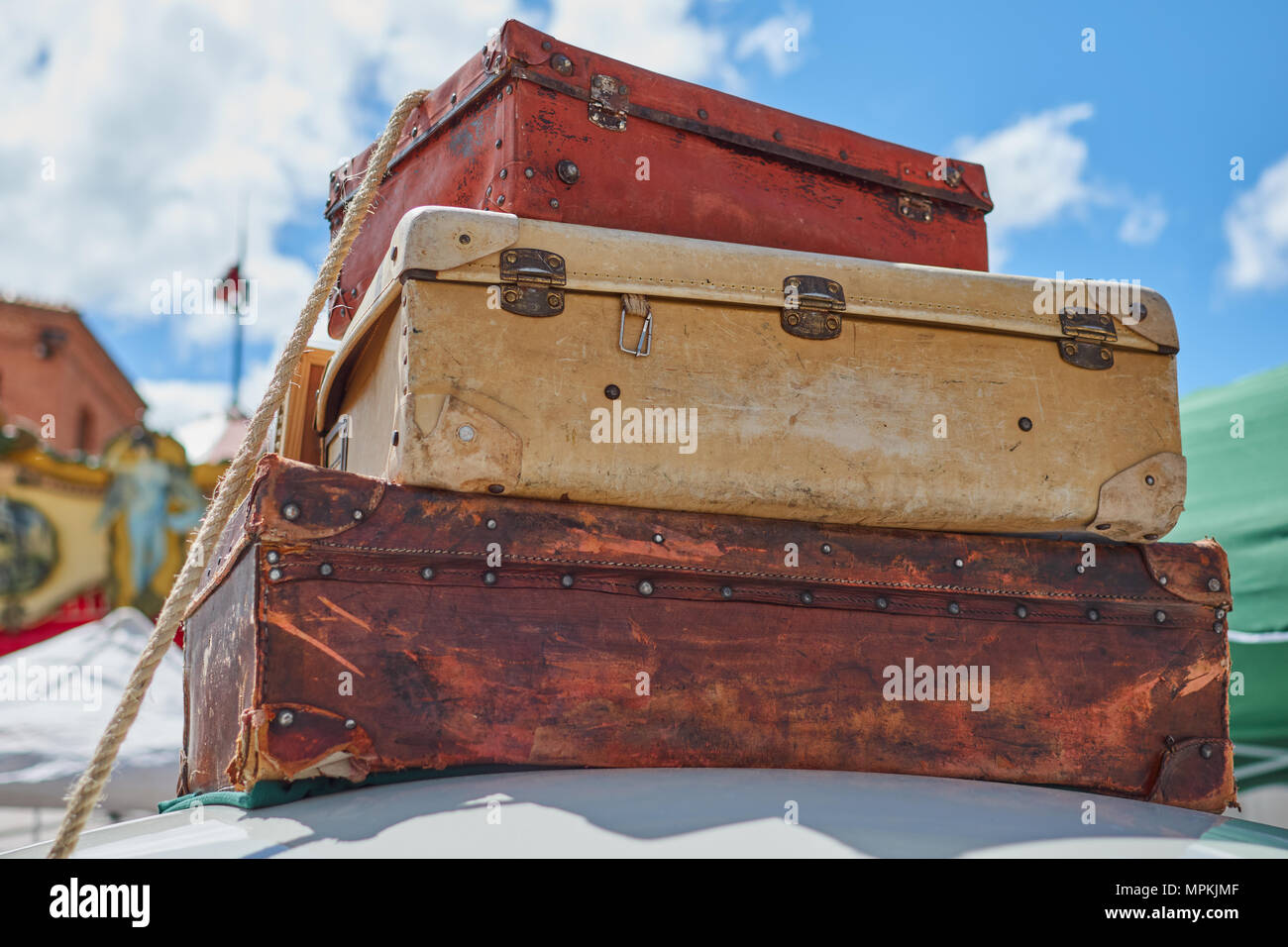 Close-up of old vintage travel suitcases fastened to the roof of a car with a rope and in the background a lovely blue sky with clouds in Segovia, Spa - Stock Image