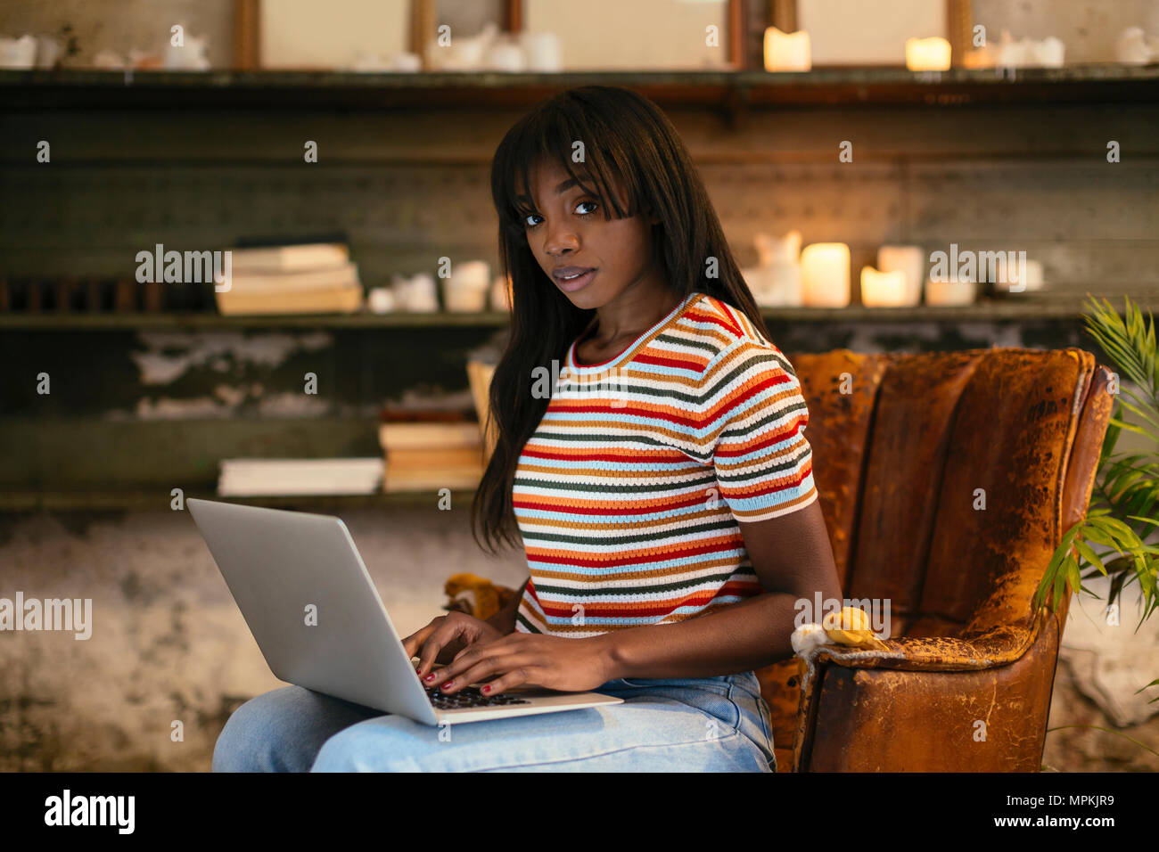 Portrait of young woman sitting on an old leather chair working on laptop in a loft - Stock Image