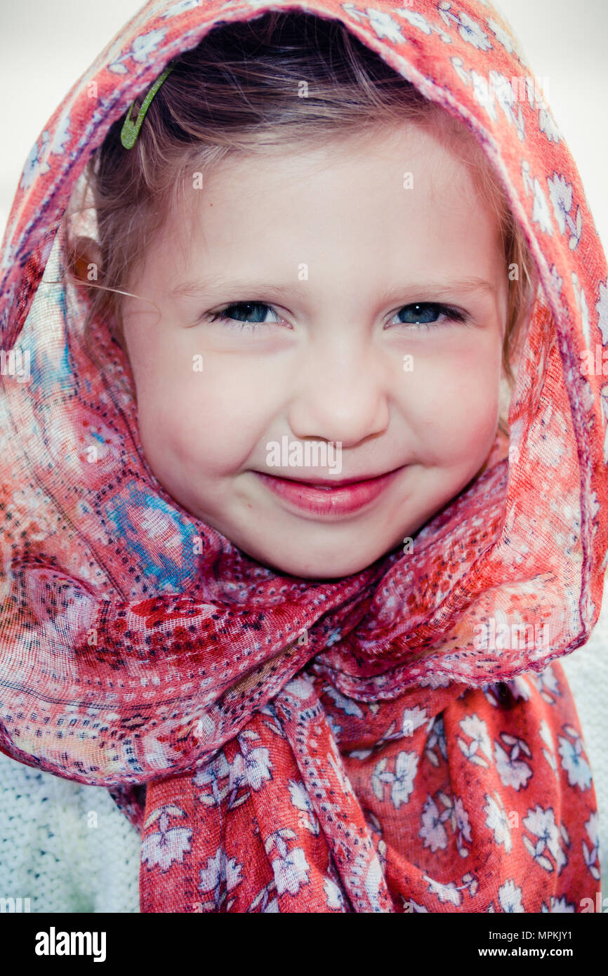 Beautiful caucasian girl child in headscarf on hot summer day - culturally appropriate / sensitive wear in Muslim / Islamic / Middle-Eastern countries - Stock Image