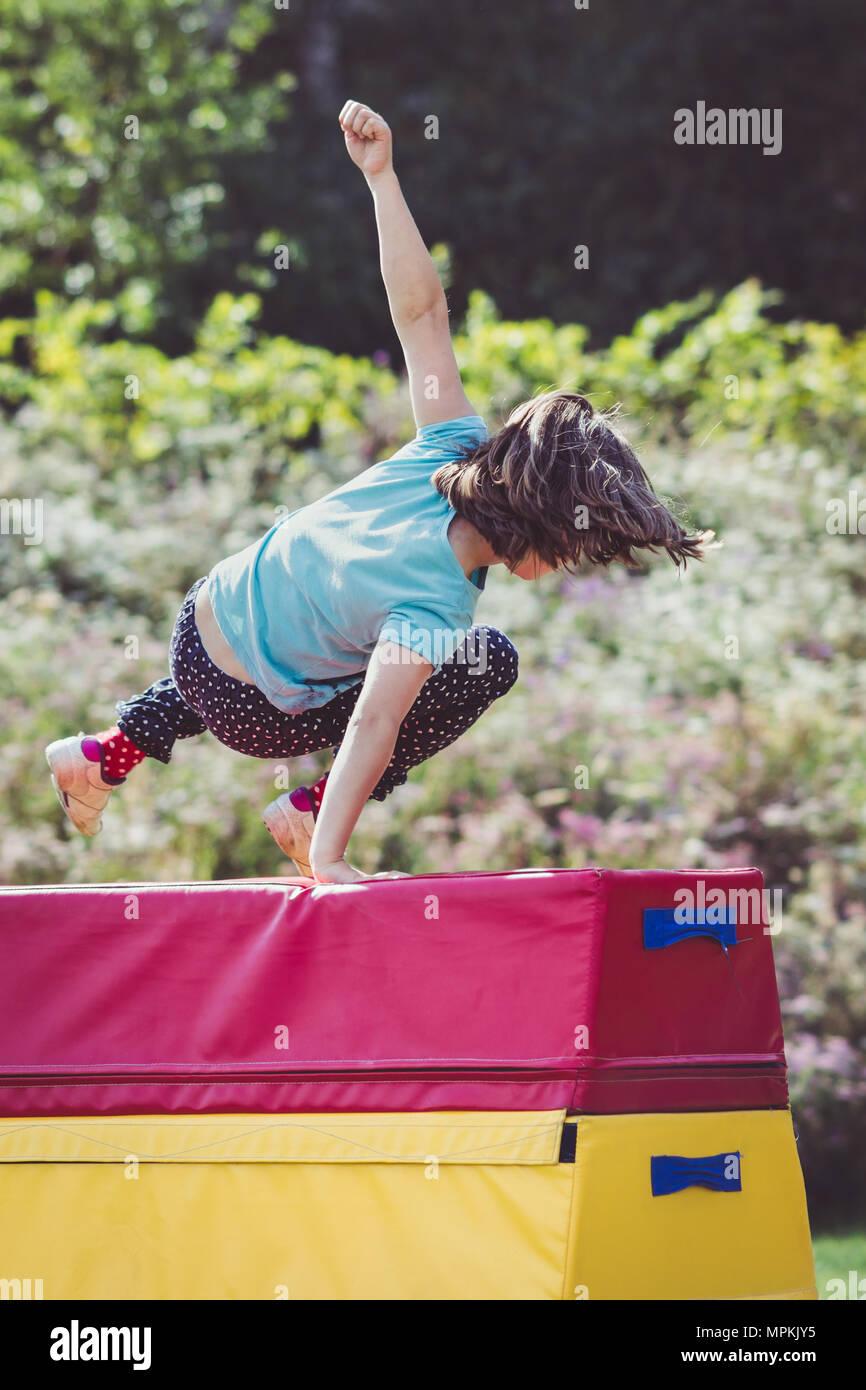 Girl Child Practicing (Practising) Gymnastics Outside on Vaulting Horse - Stock Image