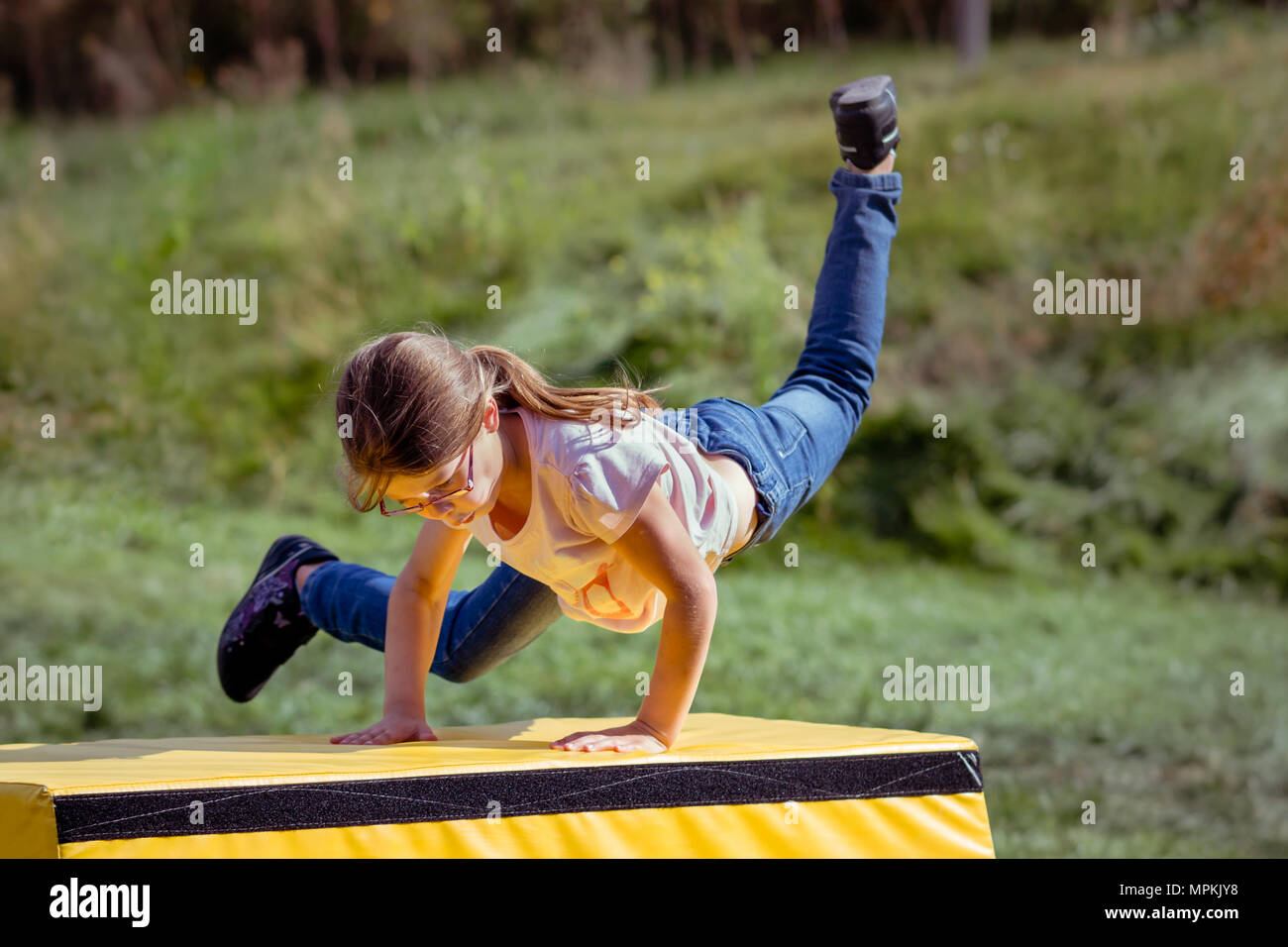 Girl Child Practicing (Practising) Parkour Gymnastics Outside on Vaulting Horse - Stock Image