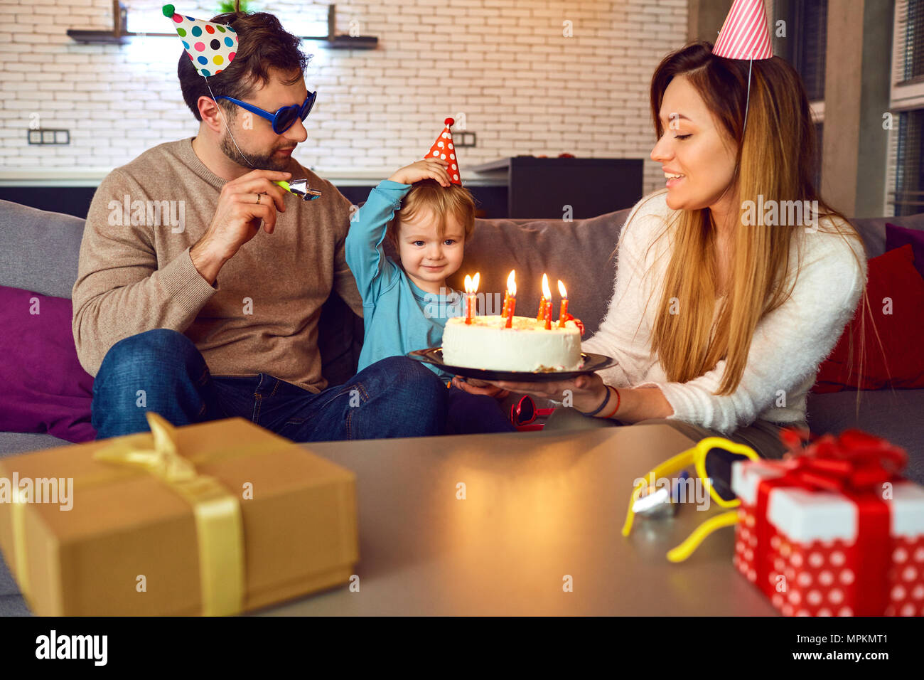 Parents with birthday cake congratulate their child. - Stock Image
