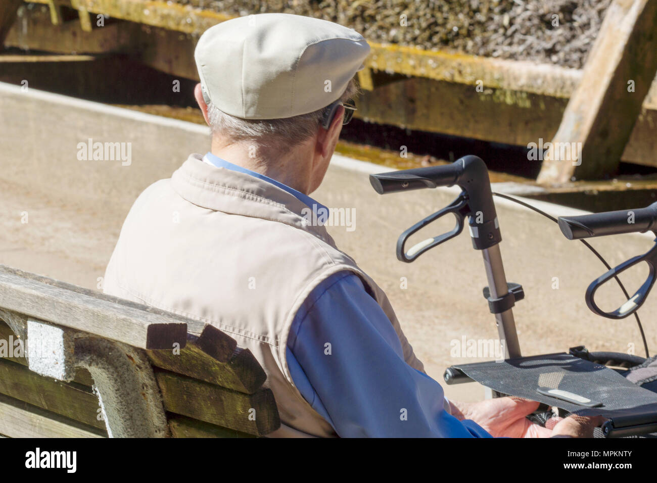 An old man is sitting in front of his wheelchair in the park and is recovering - Stock Image