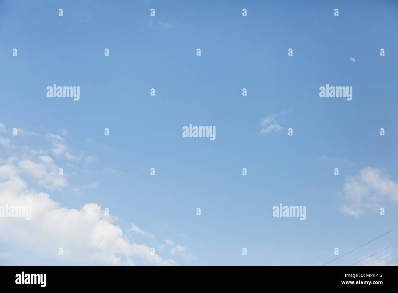Bright blue summer sky on a sunny summers day, in England , blue sky with white fluffy clouds - Stock Image
