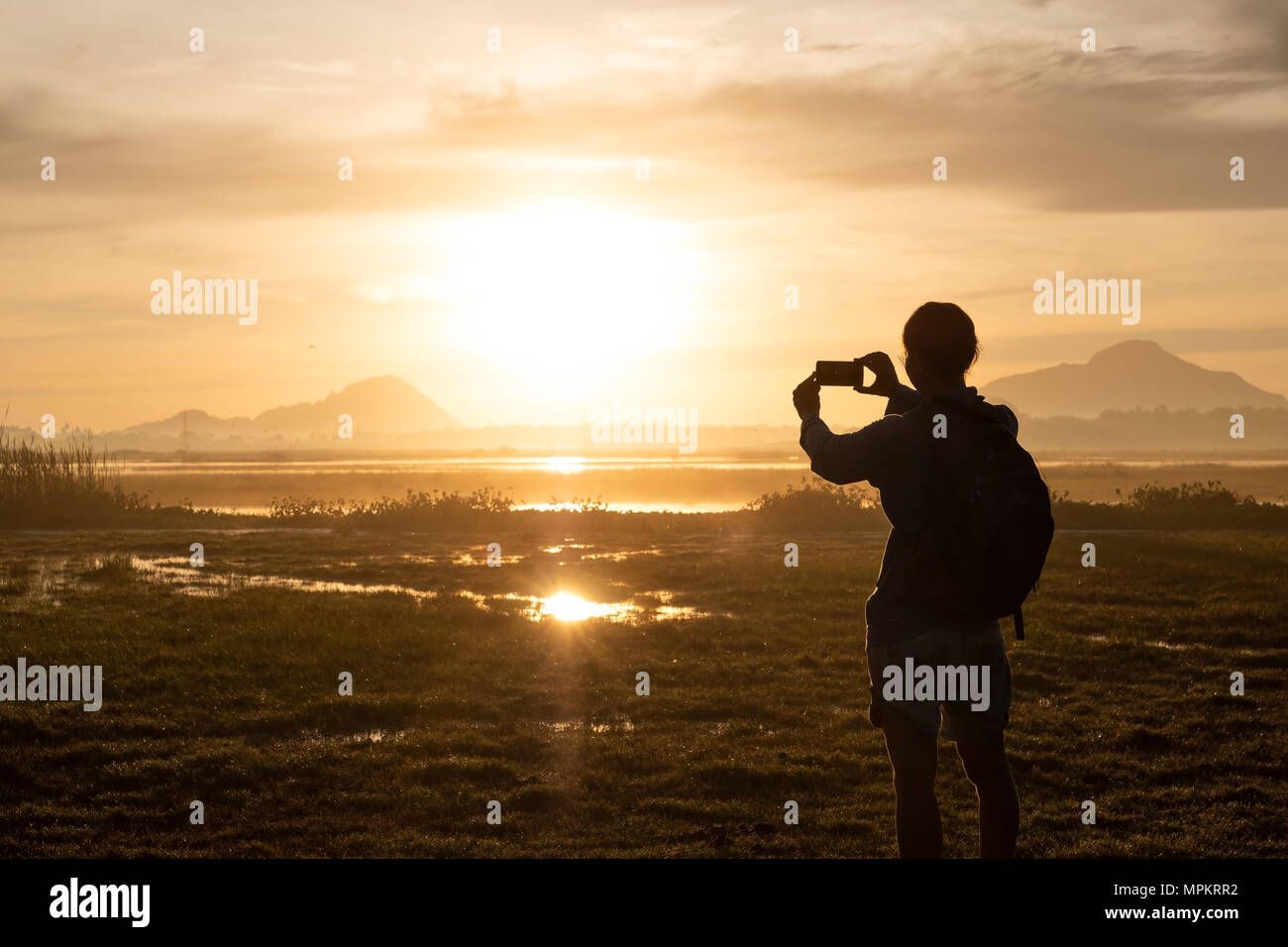 silhouette of a woman holding a smartphone taking pictures outside during sunrise or sunset. Stock Photo