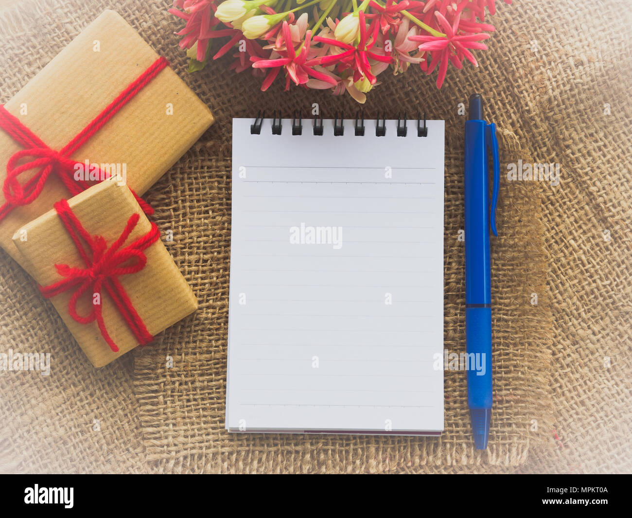 Flower Bouquet Gift And Red Flower Note Book And Blue Pen On Brown