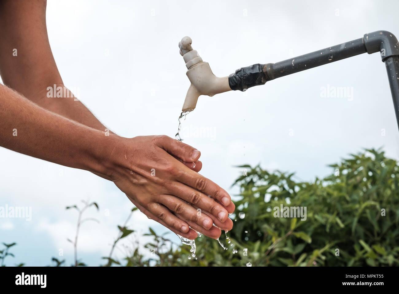 Caucasian woman washing her hands outdoor - Stock Image