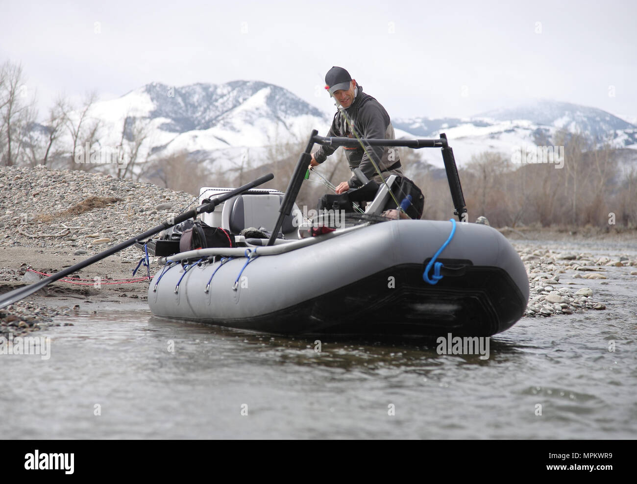 man fly fishing on river with rubber pontoon raft - Stock Image