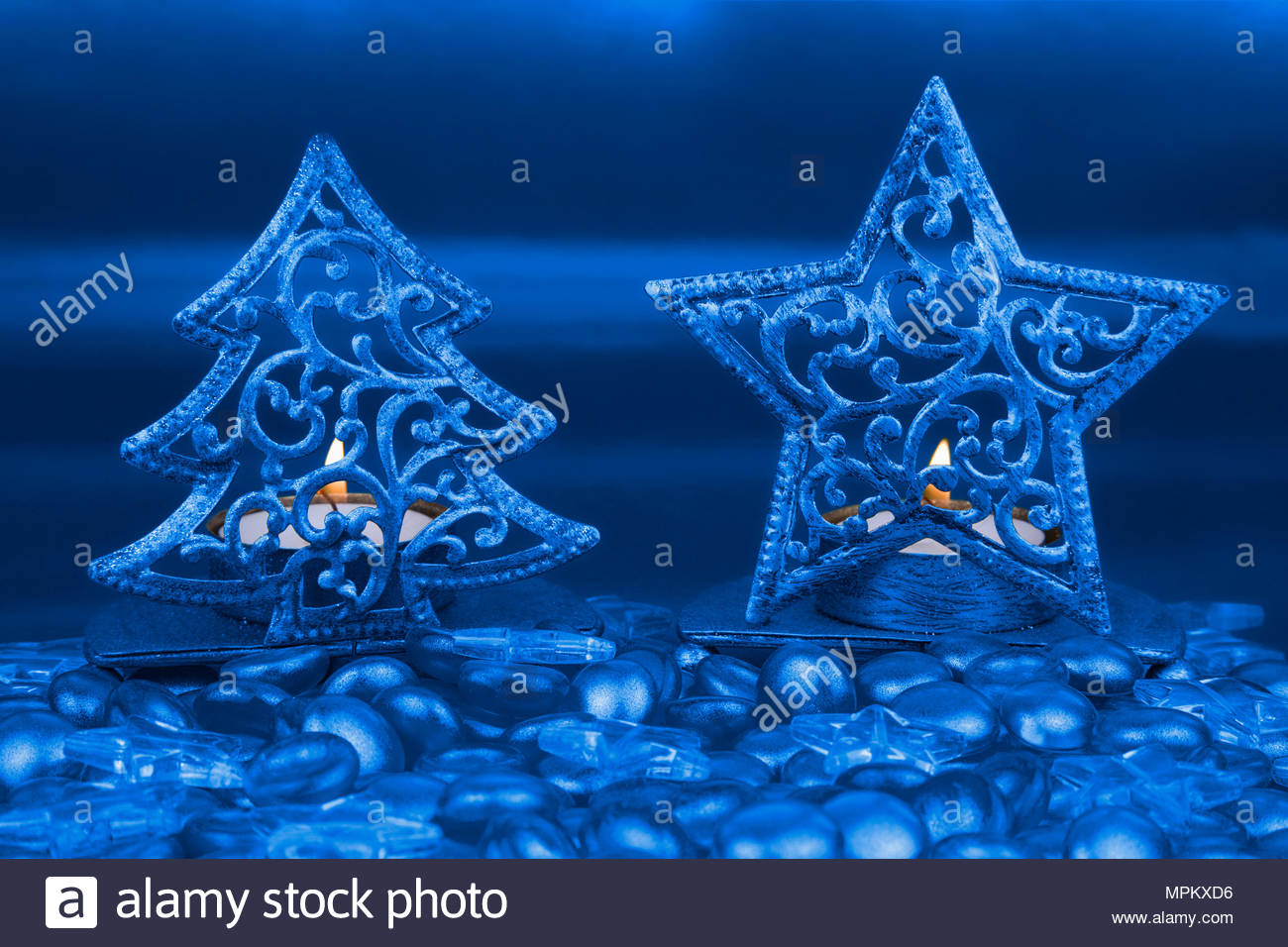 christmas tree and star shaped tea light holders with blue clear glass stars and pebbles in foreground