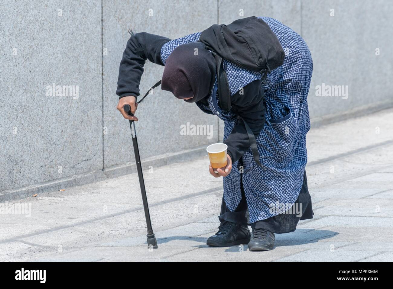 Old beggar woman bent over in a pedestrian zone, Germany - Stock Image
