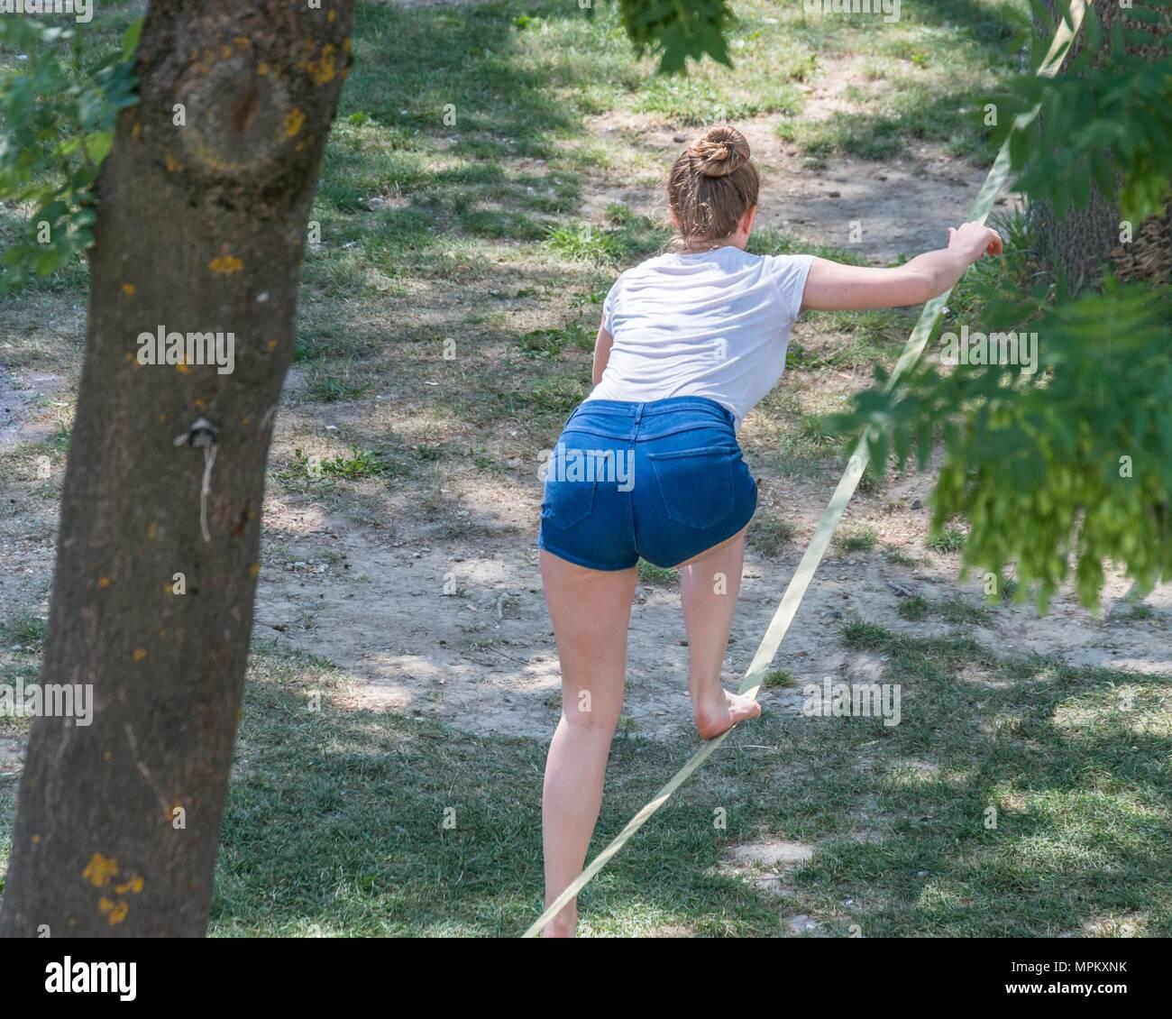 A woman balancing on a slag line, Germany - Stock Image