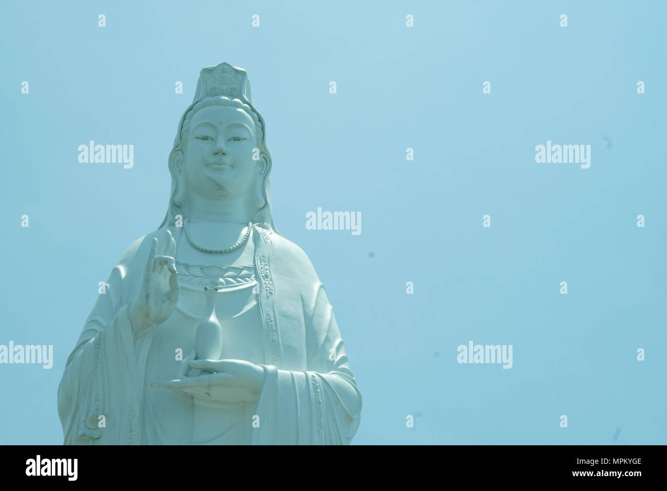 Bodhisattva statue in sky background. Royalty high quality free stock image of white bodhisattva statue in blue sky background. Da Nang city, Vietnam - Stock Image