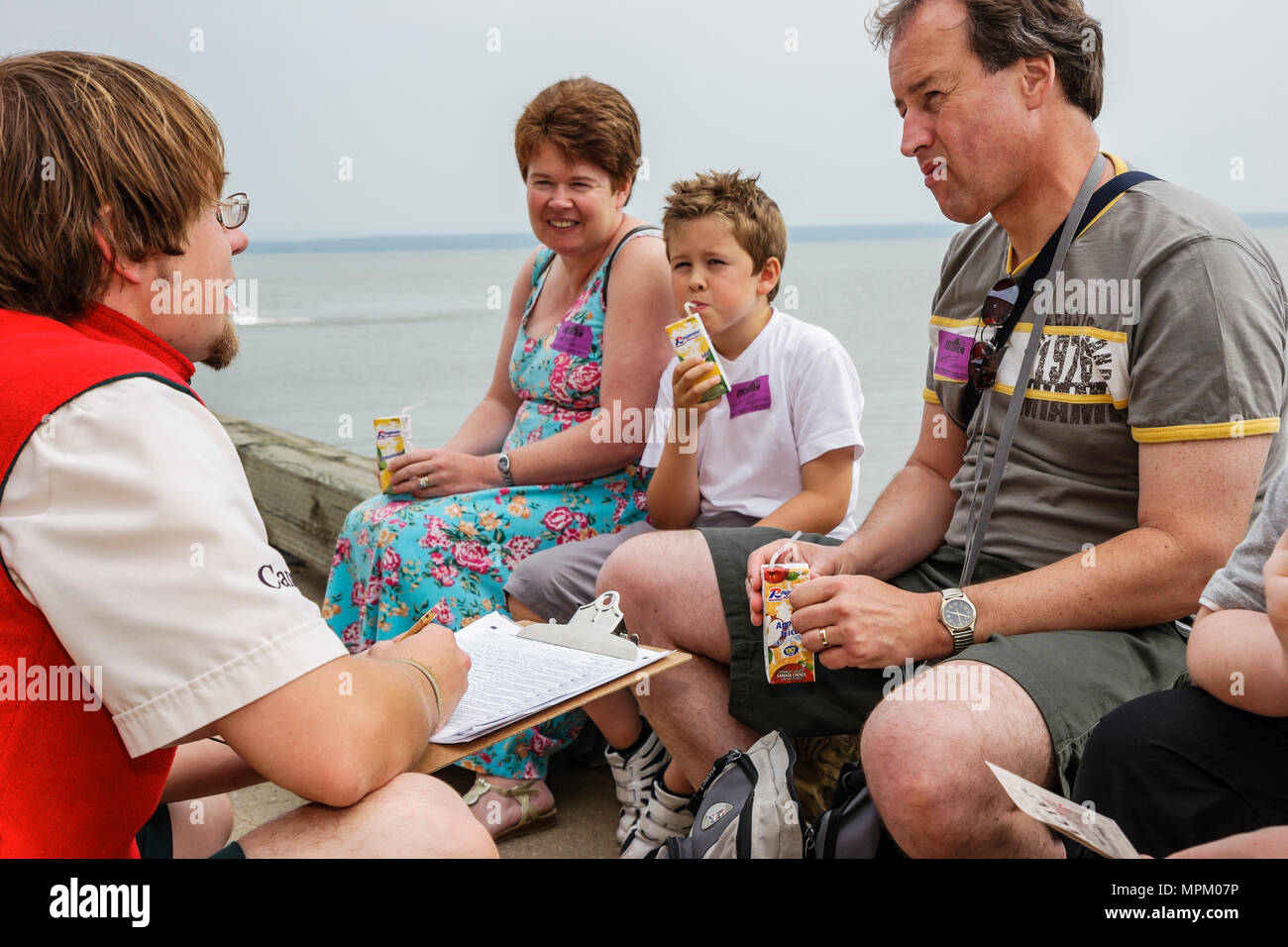 Canada Grosse Ile Irish Memorial National Historical Site park employee surveys family about visit - Stock Image