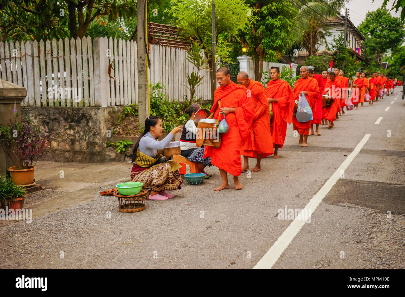 Luangprabang, Laos - December 8, 2015: Laos people offering food and things to group of Buddhist monks in morning on rural street in Luangprabang, Lao - Stock Image