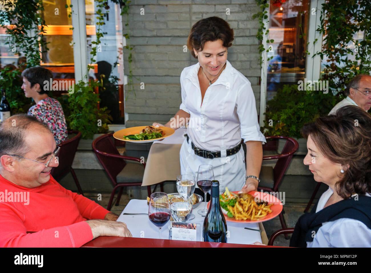 Quebec City Canada Lower Town Rue du Sault au Matelot L'Echaude Restaurant alfresco dining waitress serves food - Stock Image