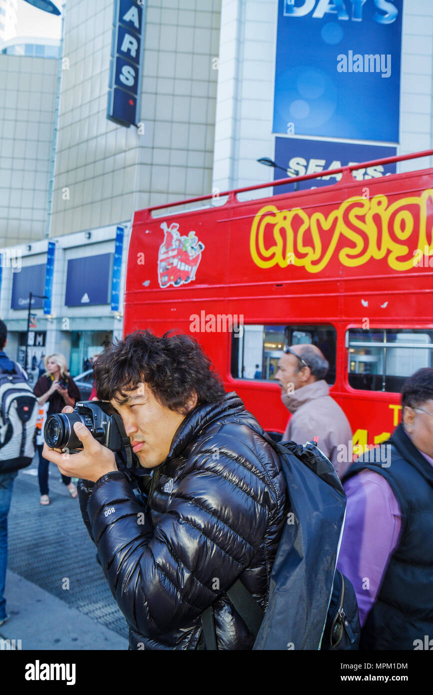 Toronto Canada Ontario Yonge Street at Dundas Downtown Yonge Yonge-Dundas Square Asian Korean man photographer SLR camera black - Stock Image