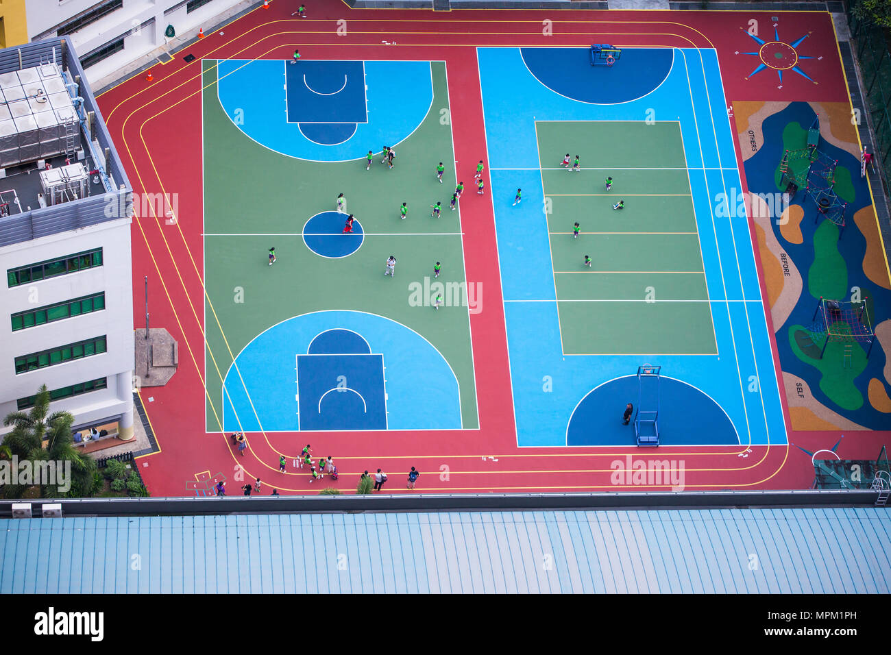 Children in green uniform running around the colourful school yard from an aerial view. - Stock Image