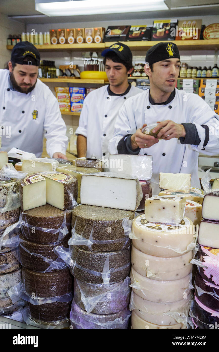 Toronto Canada Ontario St. Lawrence Market shopping vendor merchant cheese shop man sales clerk employee cheese wheel chef coat - Stock Image