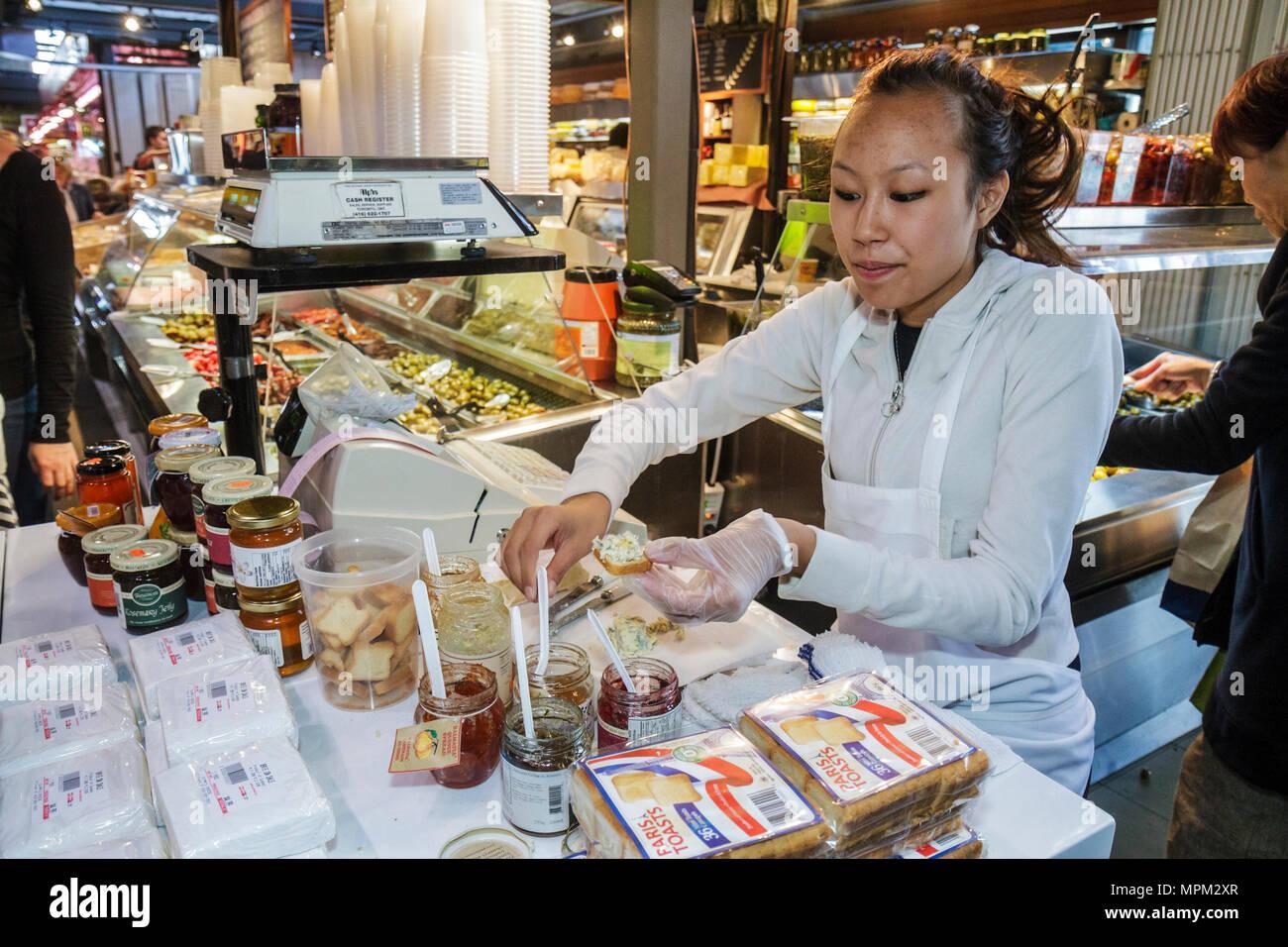 Toronto Canada Ontario St. Lawrence Market shopping vendor merchant Asian woman sales clerk employee free sample toast jelly jam - Stock Image