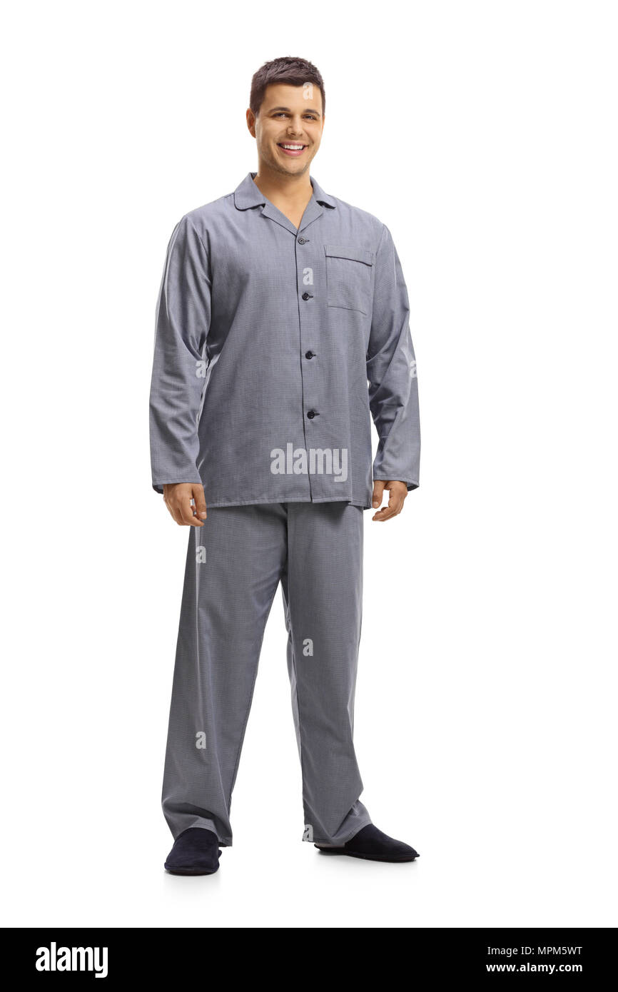 Full length portrait of a young man in pajamas smiling isolated on white background - Stock Image