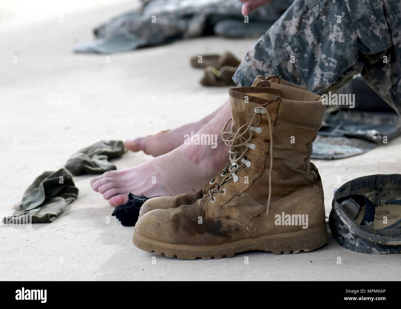An Army Reserve competitor rests and airs out his boots after a road march, which was part of the 108th Training Command (IET) Best Warrior and Drill Sergeant of the Year Competitions at Camp Bullis, Texas, March 21, 2017. (U.S. Army Reserve photo by Maj. Michelle Lunato/released) - Stock Image