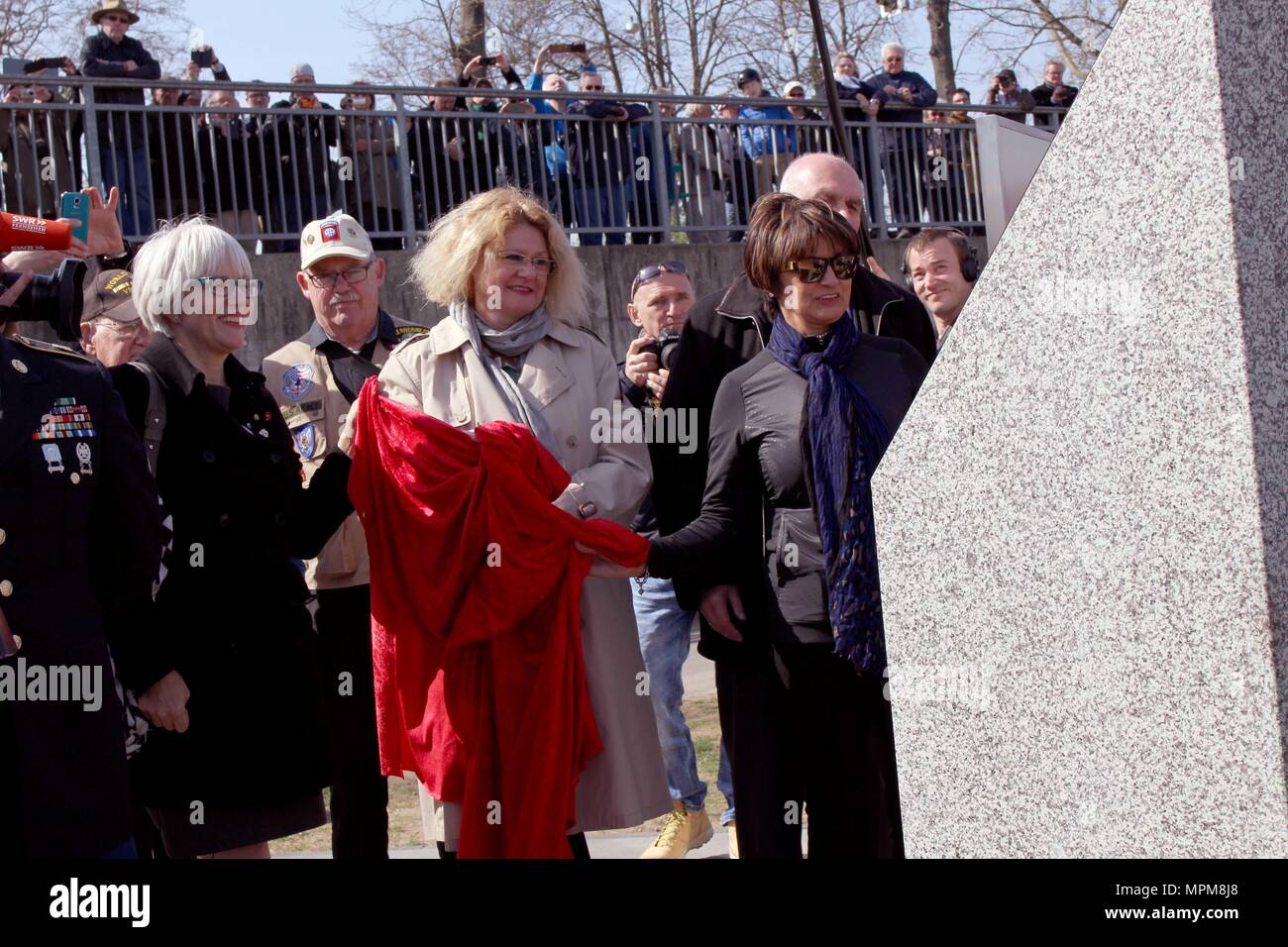 Helen Patton, left, the granddaughter of U.S. Army Gen. George Patton; Catherine Rommel, center, the granddaughter of German Field Marshall Erwin Rommel; Luci Schey, president of the Ralph and Luci Schey Foundation, examine a memorial to the Soldiers of the 249th Engineer Combat Battalion Saturday, March 24, 2017 in Nierstein Germany. (Photo by Lt. Col. Jefferson Wolfe) - Stock Image