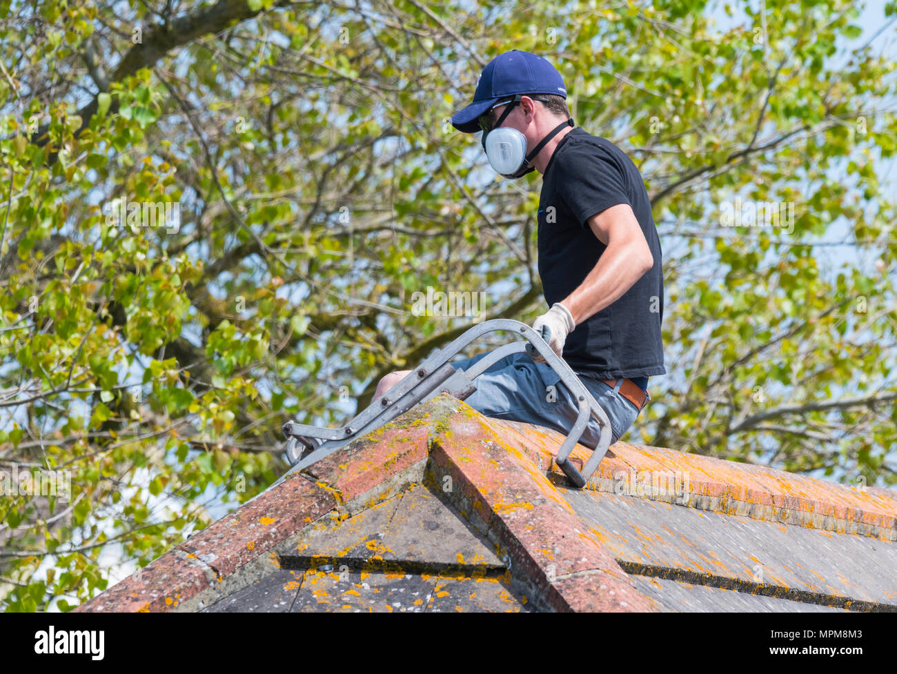 Man spraying a roof while wearing a protective respirator mask, in the UK. - Stock Image