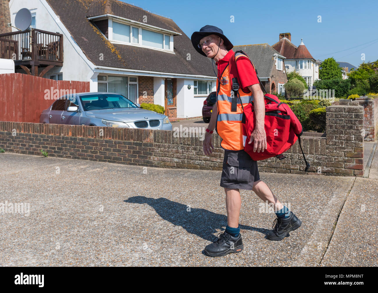 British postman wearing shorts walking in a residential area carrying a red satchel of letters, for morning deliveries in West Sussex, England, UK. - Stock Image