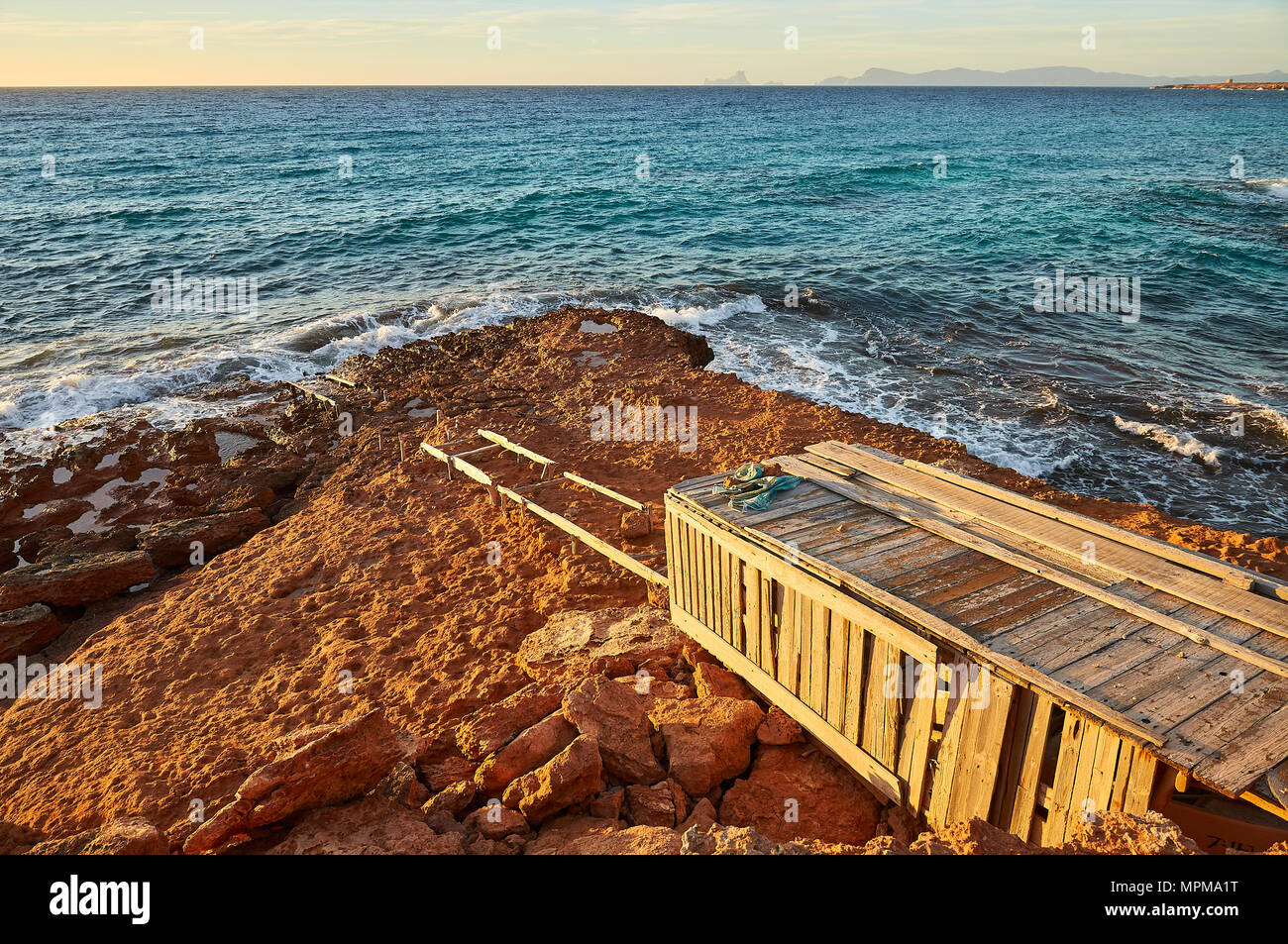 Traditional dry dock by the sea near Cala Saona with Es Vedrá islet and Ibiza island in the distance from Formentera (Balearic Islands, Spain) - Stock Image