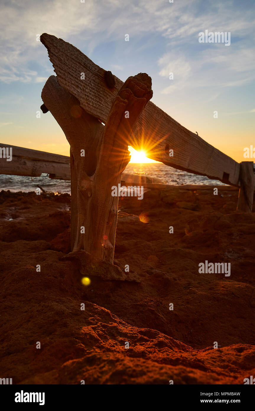 Traditional wood dry dock stand by the sea with sunbeam at sunset at Caló d'en Trull near Cala Saona in Formentera (Balearic Islands, Spain) - Stock Image