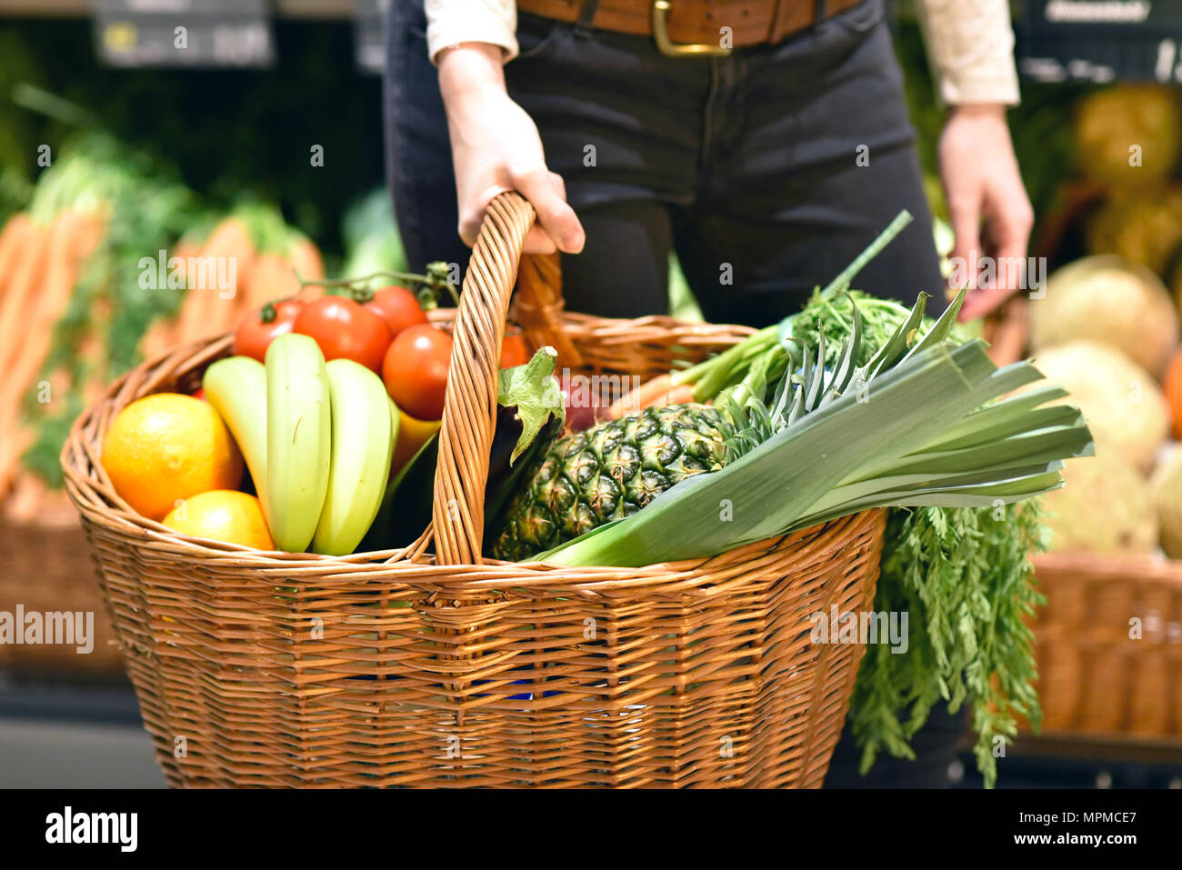 grocery shopping in the supermarket - filled shopping trolley with fresh fruit and vegetables - Stock Image
