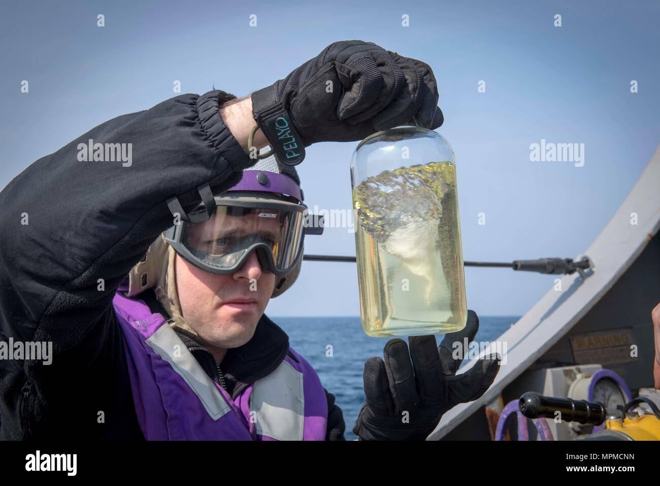 WATERS EAST OF THE KOREAN PENINSULA (March 22, 2017) Gas Turbine Systems Technician (Mechanical) 2nd Class Taylor Poling, assigned to the Arleigh Burke-class guided-missile destroyer USS Stethem (DDG 63), checks JP-5 fuel for impurities prior to a passenger transport with the Nimitz-class aircraft carrier USS Carl Vinson (CVN 70) during Foal Eagle (FE) 17. FE 17 is a series of annual training events designed to increase readiness to defend the ROK, protect the region, and maintain stability in the Korean Peninsula. (U.S. Navy photo by Mass Communication Specialist 2nd Class Ryan Harper/ Releas - Stock Image