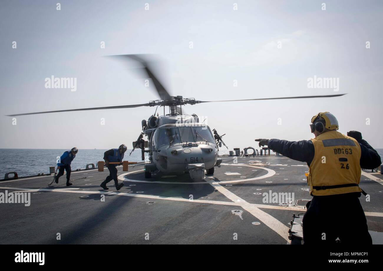 WATERS EAST OF THE KOREAN PENINSULA (March 22, 2017) Boatswains Mate 2nd Class Javier Garza, assigned to the Arleigh Burke-class guided-missile destroyer USS Stethem (DDG 63), gives the signal to secure a MH-60 helicopter during a passenger transport with the Nimitz-class aircraft carrier USS Carl Vinson (CVN 70) during Foal Eagle (FE) 17. FE 17 is a series of annual training events designed to increase readiness to defend the ROK, protect the region, and maintain stability in the Korean Peninsula. (U.S. Navy photo by Mass Communication Specialist 2nd Class Ryan Harper/ Released) - Stock Image