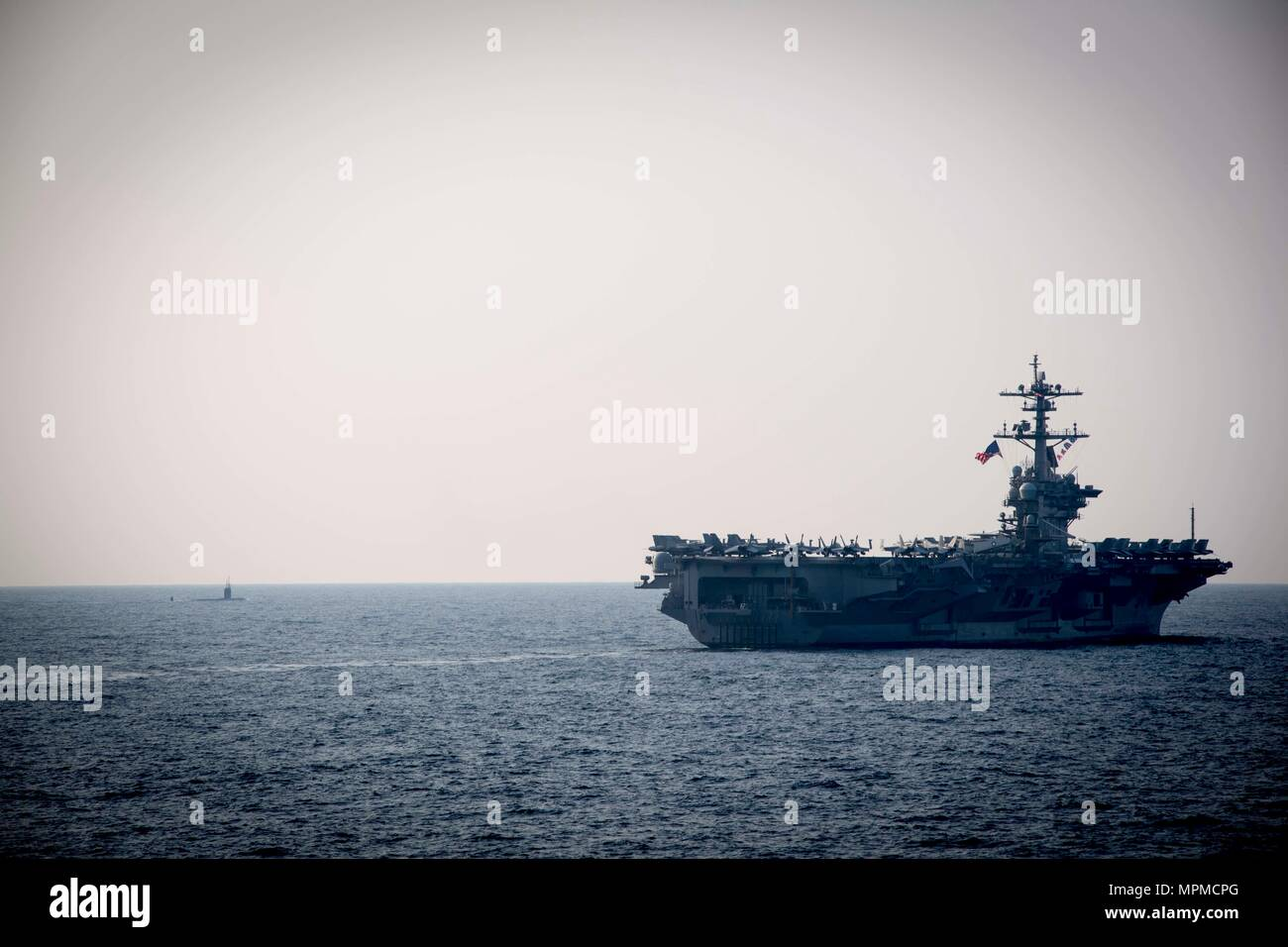 WATERS EAST OF THE KOREAN PENINSULA (March 22, 2017) The Nimitz-class aircraft carrier USS Carl Vinson (CVN 70) and blanksubmarine steam ahead of the Arleigh Burke-class guided-missile destroyer USS Stethem (DDG 63) during a surface maenuvers exercise with several other U.S. and Republic of Korea Navy ships and submarines during Foal Eagle (FE) 17. FE 17 is a series of annual training events designed to increase readiness to defend the ROK, protect the region, and maintain stability in the Korean Peninsula. (U.S. Navy photo by Mass Communication Specialist 2nd Class Ryan Harper/ Released) - Stock Image