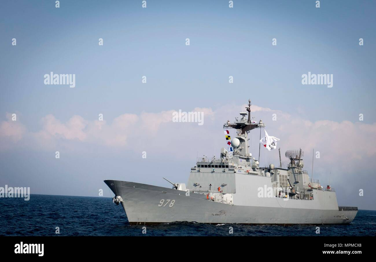 WATERS EAST OF THE KOREAN PENINSULA (March 22, 2017) The Republic of Korea Navy Chungmugong Yi Sun-sin-class guided-missile destroyer ROKS Wang Geon (DDG 978) steams behind the Arleigh Burke-class guided-missile destroyer USS Stethem (DDG 63) as the ships participate in surface maneuvers with several other U.S. and Republic of Korea Navy ships and submarines during Foal Eagle (FE) 17. FE 17 is a series of annual training events designed to increase readiness to defend the ROK, protect the region, and maintain stability in the Korean Peninsula. (U.S. Navy photo by Mass Communication Specialist  - Stock Image