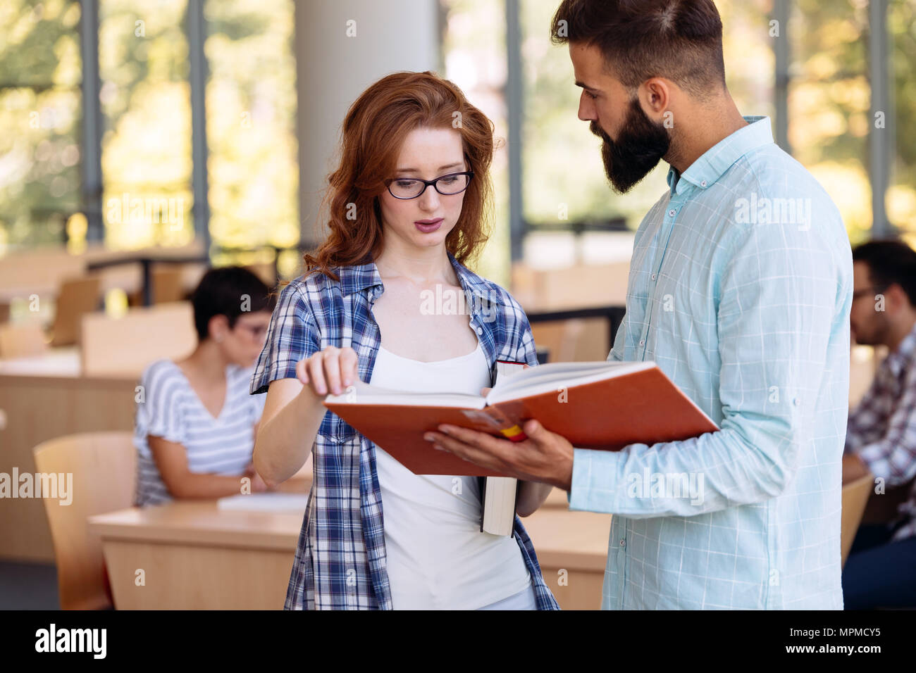 Young woman and man studying for an exam. - Stock Image