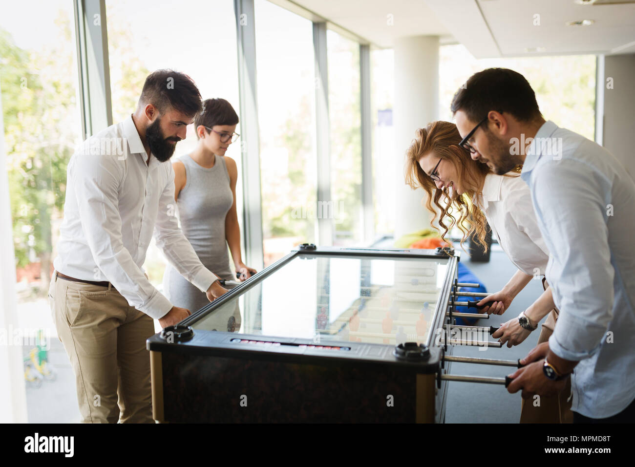 Coworkers playing table football on break from work - Stock Image