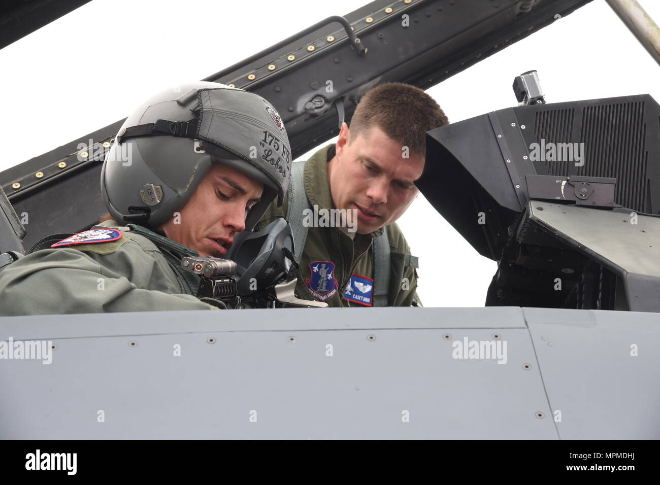 Capt. Casey Minor, 175th Fighter Squadron pilot, explains the controls and instruments of the F-16 to Professional Bull Rider, Stetson Lawrence, before his F-16 orientation ride at Joe Boss Field, S.D. on March 29, 2017. The PBR organization visited the 114th Fighter Wing as a part of a community outreach program. (Air National Guard photo by Staff Sgt. Duane Duimstra/Released) - Stock Image