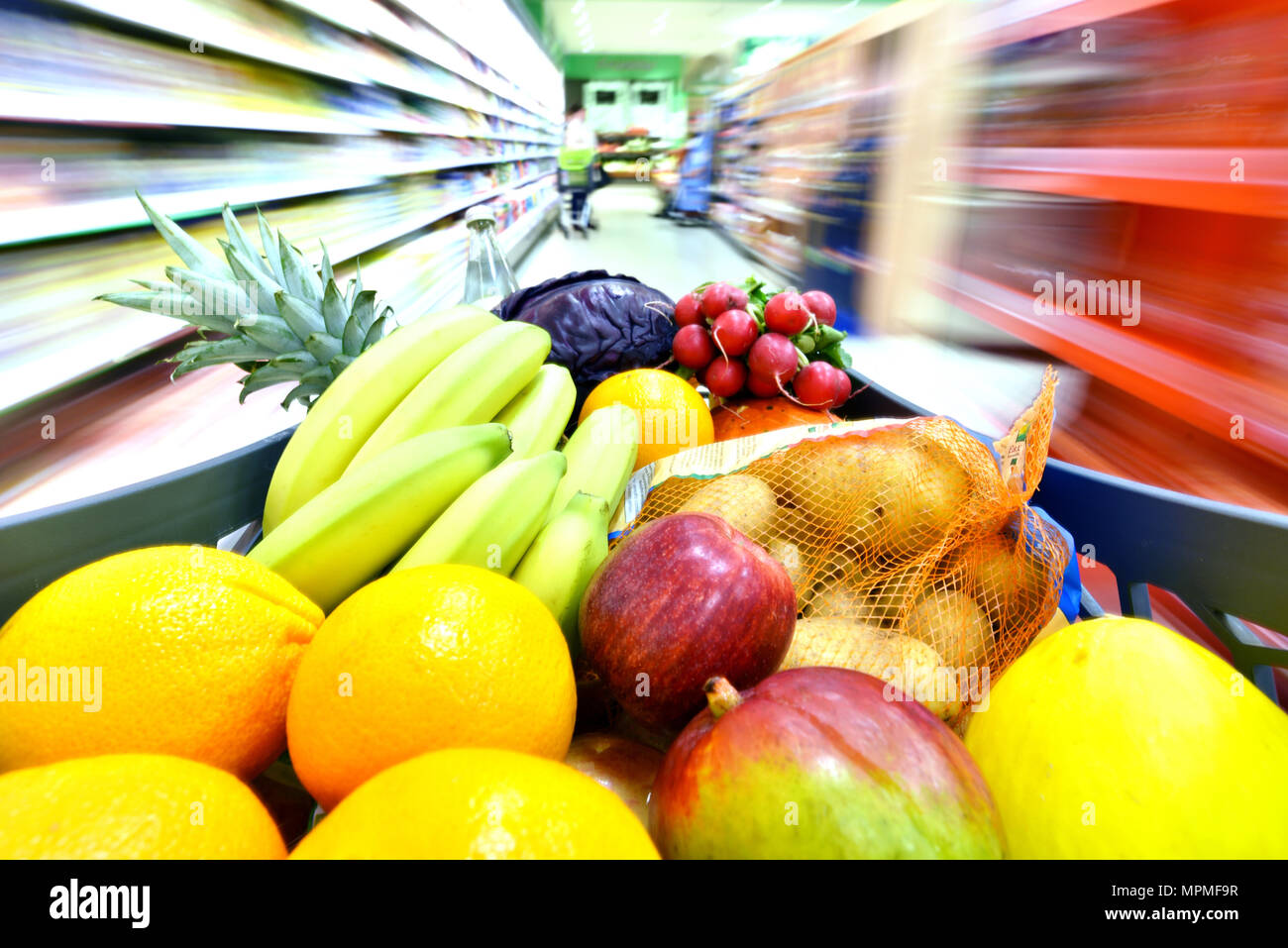 grocery shopping in the supermarket - filled shopping trolley with fresh fruit and vegetables Stock Photo
