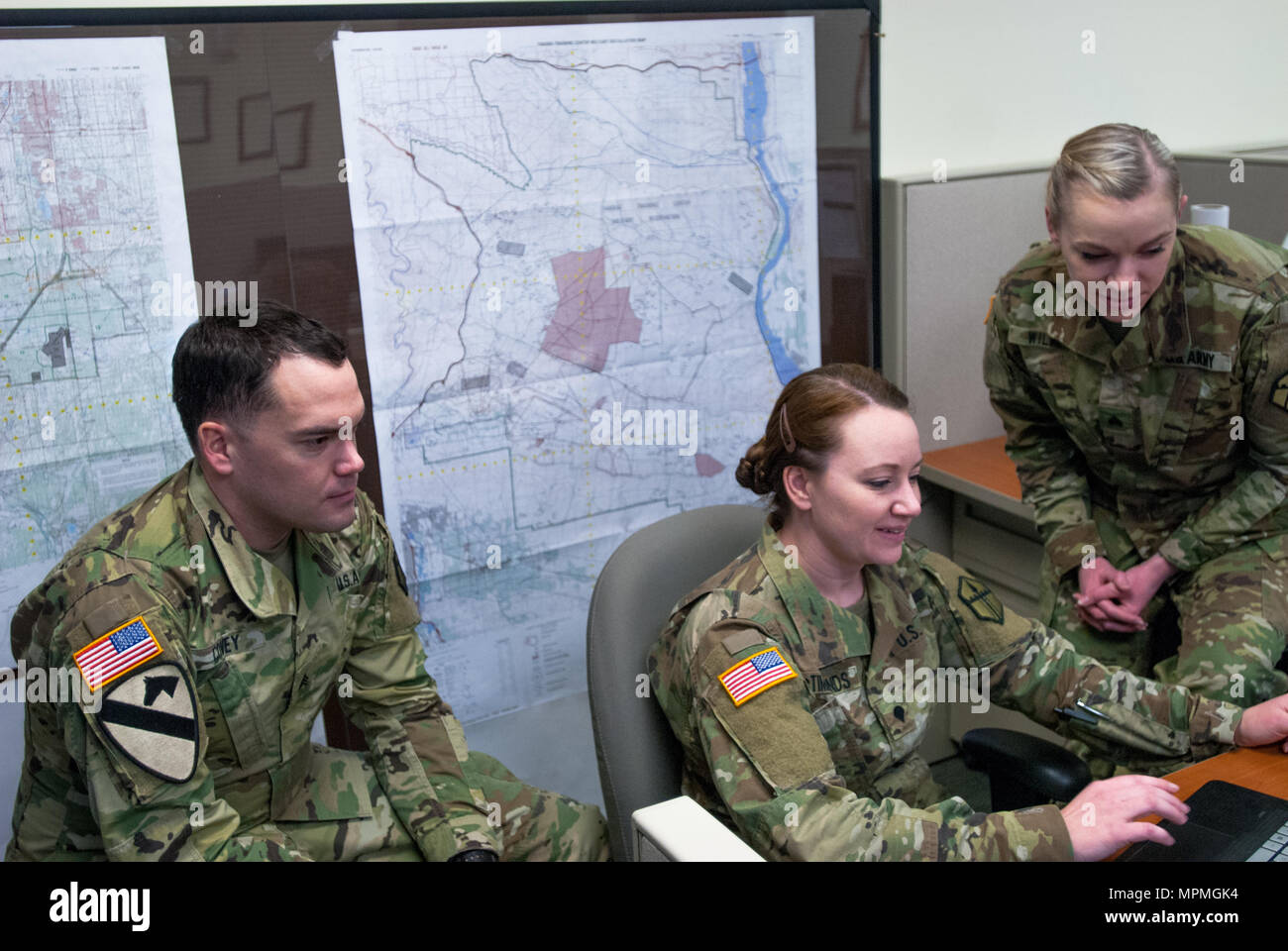 From left: Sgt. Morgan T. Wilken, Spc. Tara M. McTimmonds, Sgt. Noel A. Covey, work together to produce a Combined Obstacle Overlay, Joint Base Lewis-McChord, Wash. February 12, 2017. Geospatial engineers produce the maps that will support the commander's next mission, and are a vital component of the Army, Army Reserve, and Total Force (U.S. Army Reserve photo by Spc. Sean Harding/Released). - Stock Image