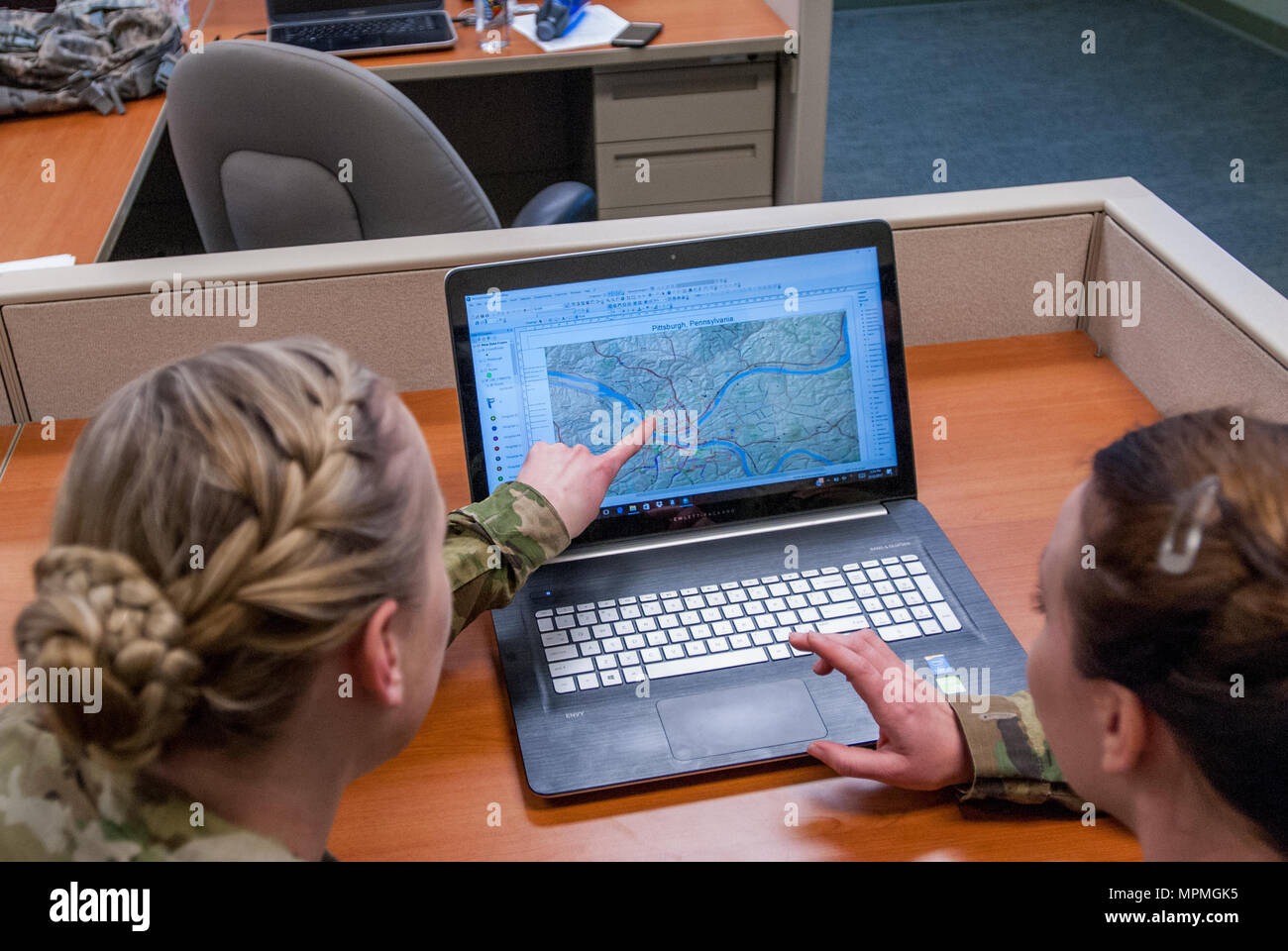 Sgt. Morgan T. Wilken identifies a location in ArcMap at the 301st Maneuver Enhancement Brigade headquarters, Joint Base Lewis-McChord, Washington, Feburary 12, 2017. Geospatial engineers produce the maps that will support the commander's next mission, and are a vital component of the Army, Army Reserve, and Total Force (U.S. Army Reserve photo by Spc. Sean Harding/Released). - Stock Image